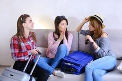 Filles mignonnes partant en voyage et préparant des valises sur le divan dedans à l'arrière Photo libre de droits