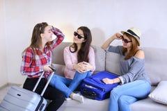 Filles mignonnes partant en voyage et préparant des valises sur le divan dedans à l'arrière Image stock