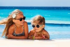 Filles mignonnes prenant un bain de soleil au bord de la piscine photographie stock libre de droits