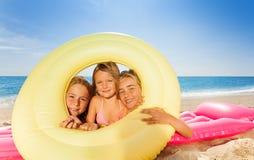 Filles mignonnes regardant par l'anneau en caoutchouc la plage Photos stock