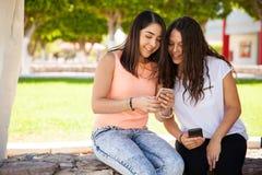Filles mignonnes regardant un smartphone Photographie stock