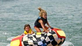 Filles mignonnes sur le tube derrière le bateau image libre de droits