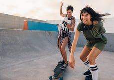 Filles montant sur des planches à roulettes et ayant l'amusement au parc de patin Images libres de droits