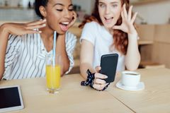 Filles multi-ethniques à l'aide du smartphone Image libre de droits