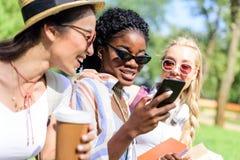 Filles multi-ethniques à l'aide du smartphone et buvant du café de la tasse de papier dans le parc Photographie stock