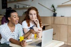 Filles multi-ethniques avec l'ordinateur portable et la carte de crédit Photographie stock libre de droits