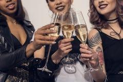 Filles multi-ethniques de sourire faisant tinter avec des verres de champagne à la partie Photographie stock libre de droits