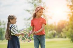 Filles multi-ethniques de sourire jouant avec le jouet au coucher du soleil en parc Image libre de droits