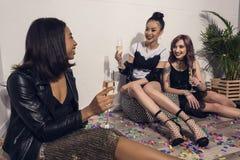 Filles multi-ethniques de sourire reposant et buvant du champagne à la partie Image stock