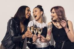Filles multi-ethniques heureuses buvant du champagne à la partie Photographie stock
