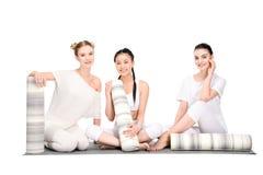 Filles multi-ethniques heureuses se reposant après la formation et la séance de yoga avec des tapis de yoga et regardant l'appare Photos stock