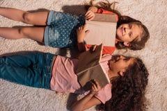 Filles multiculturelles avec des livres dans des mains se trouvant sur le plancher à la maison Image stock