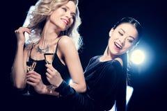 Filles multiculturelles de charme ayant l'amusement et buvant du champagne à la partie Image stock