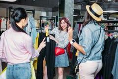 Filles multiculturelles de hippie choisissant des vêtements dans la boutique Image stock