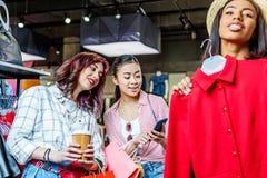 Filles multiculturelles de hippie choisissant des vêtements et à l'aide du smartphone dans la boutique Photographie stock