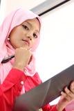 Filles musulmanes retenant un fichier d'édition image stock