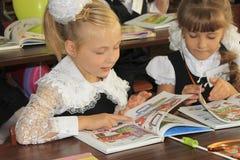 Filles non identifiées de la classe junior, regardant le nouveau tex Photographie stock libre de droits