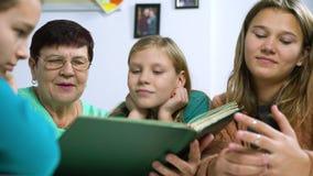 Filles observant le vieil album photos avec leur grand-mère clips vidéos