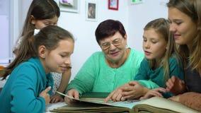 Filles observant le vieil album photos avec leur grand-mère banque de vidéos