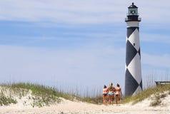 Filles par le phare de plage Photographie stock libre de droits