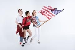 Filles posant avec le drapeau américain d'isolement sur le blanc Photo stock