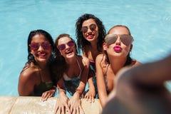 Filles posant pour le selfie de groupe dans la piscine Image stock