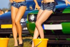 Filles posant sur la voiture de sport images stock