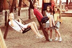 Filles positives et garçons balançant sur le terrain de jeu Photo libre de droits