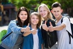 Filles positives et garçons posant avec des pouces  Images libres de droits