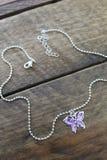 Filles pourpres et collier argenté de papillon d'isolement sur un fond en bois Image stock