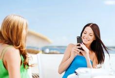 Filles prenant la photo en café sur la plage Photo stock