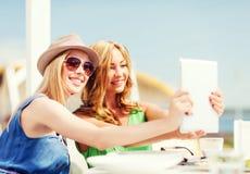Filles prenant la photo en café sur la plage Images stock