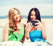 Filles prenant la photo en café sur la plage Image stock