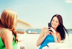 Filles prenant la photo en café sur la plage Images libres de droits