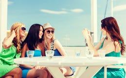 Filles prenant la photo en café sur la plage Photographie stock libre de droits