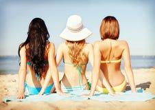 Filles prenant un bain de soleil sur la plage Photos libres de droits