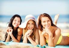 Filles prenant un bain de soleil sur la plage Image stock
