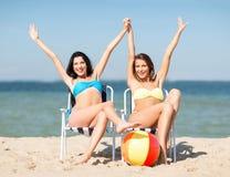 Filles prenant un bain de soleil sur les chaises de plage Photographie stock libre de droits