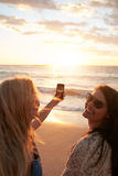 Filles prenant une photo du coucher du soleil avec le téléphone portable Image libre de droits