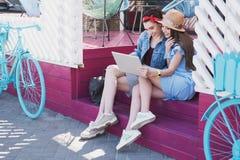 Filles regardant dans l'ordinateur portable tout en se reposant sur une terrasse Image stock