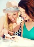 Filles regardant le smartphone en café Image libre de droits
