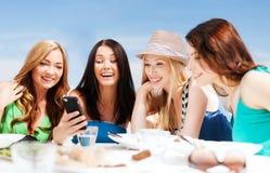 Filles regardant le smartphone en café sur la plage Photos stock