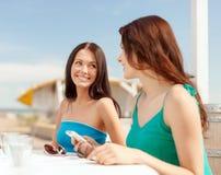 Filles regardant le smartphone en café sur la plage Photos libres de droits