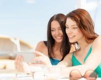 Filles regardant le smartphone en café sur la plage Image libre de droits