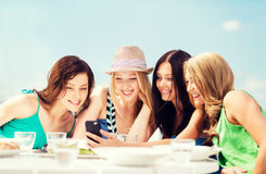 Filles regardant le smartphone en café sur la plage Images stock
