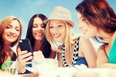 Filles regardant le smartphone en café sur la plage Images libres de droits