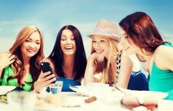 Filles regardant le smartphone en café sur la plage Photographie stock libre de droits