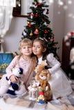 Filles reposant la joue à la joue sous l'arbre de Noël Images libres de droits