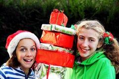 Filles retenant la pile des présents de Noël Photographie stock libre de droits