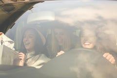 Filles retournant des achats Jeunes filles montant la voiture Images stock